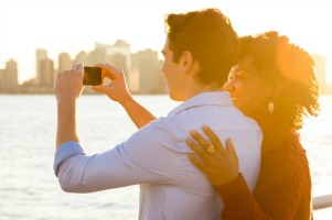 Romantic couple tourists taking photo and having fun. Young happy couple taking photo of the river and skyscrapers with smartphone. Happy young couple embracing and taking photo at river side during sunset.