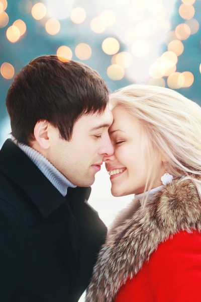 Christmas romantic sensual couple in love to cold winter day over celebration bokeh, gentle kiss moment
